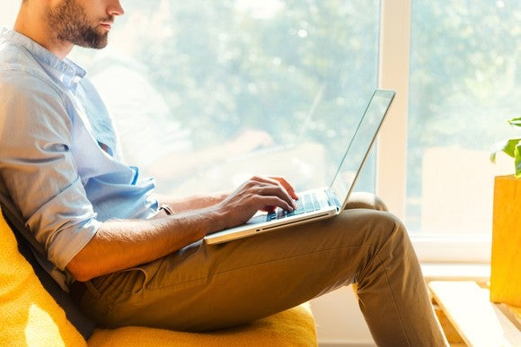 A man works on his laptop sitting on a couch.