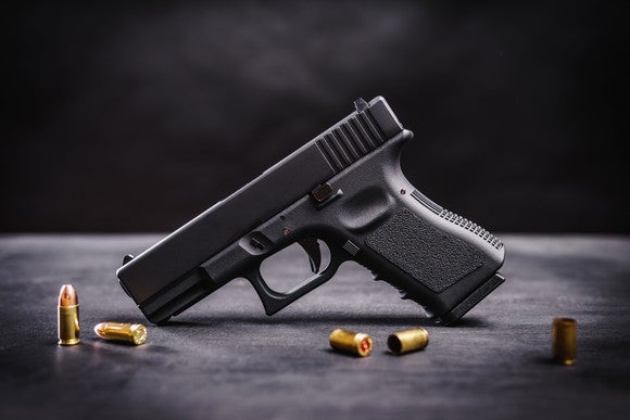 Handgun on a table with assortment of bullets.