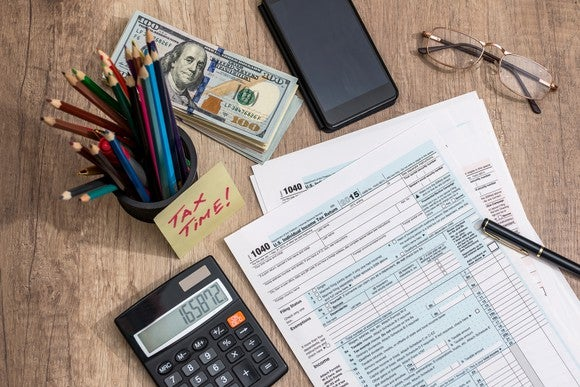 Tax forms on table, next to calculator, stack of money, glasses, and cup of pencils.