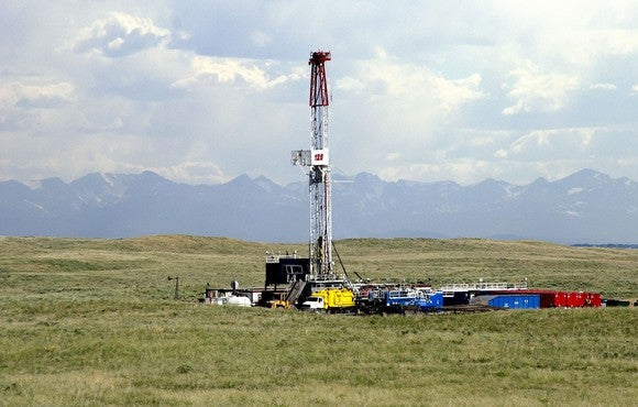 Drilling rig and associated equipment on a pasture with the Front Range and clouds in the background.