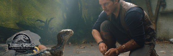 Actor Chris Pratt crouches besides a baby velociraptor dinosaur.