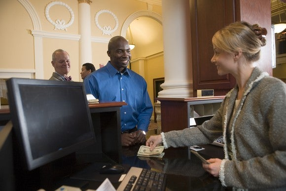 A bank teller smiles at a customer as she counts out money for him.