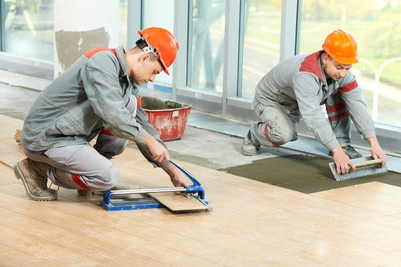 Two construction workers laying flooring.