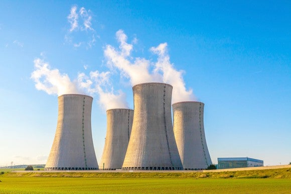 Four nuclear reactors with smoke billowing out of their stacks into a blue sky.