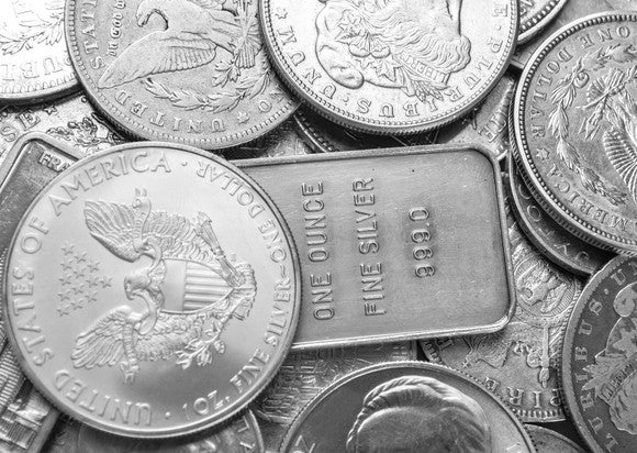 A spread-out pile of silver coins and bars.
