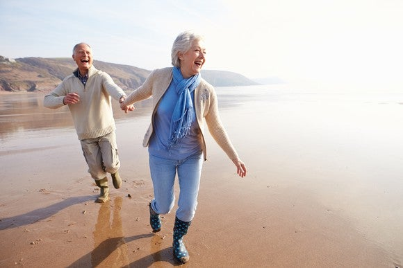 Senior couple holding hands and running along the beach