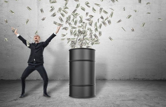 A smiling man raises his arms next to an oil barrel above which is a cloud of paper money.