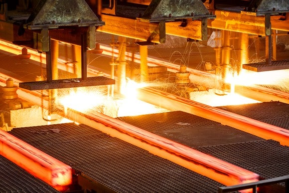 Hot steel on conveyor in steel mill.