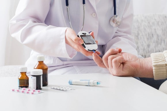 Doctor helping patient take blood sugar level near near medications on table