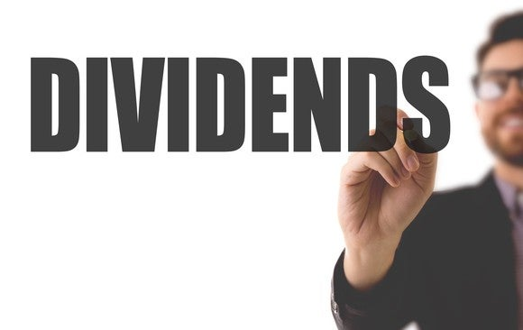 A man writing the word dividends