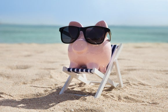 A piggy bank with sunglasses sits on a beach chair on a beach with a body of water in the background.