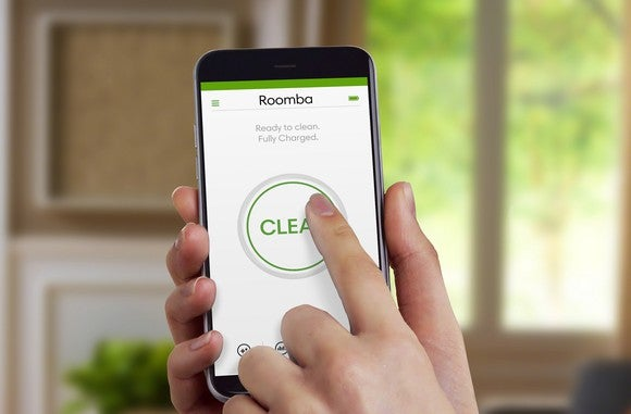 "Hand holding a smartphone, pushing a ""CLEAN"" button on iRobot's mobile app"