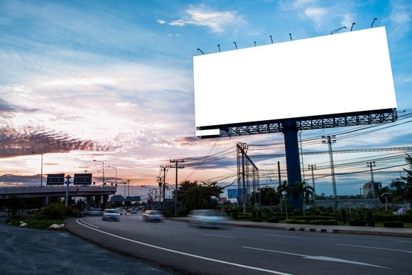 A billboard on the side of a busy highway.