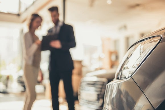 A car dealer shows a customer a car.