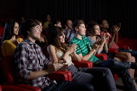Movie theater with a full crowd of clapping movie viewers.