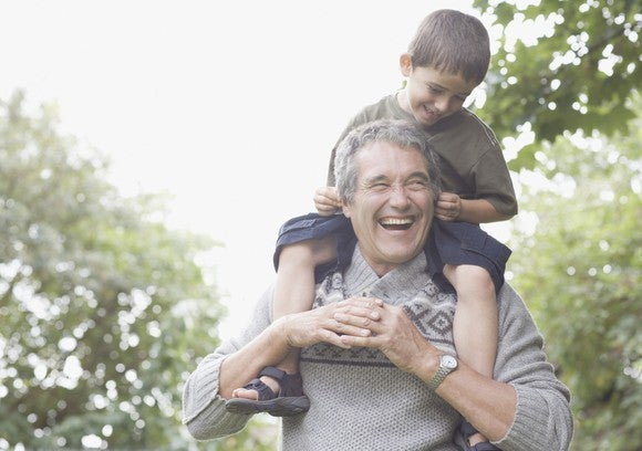 Smiling grandfather carrying grandson on his shoulders
