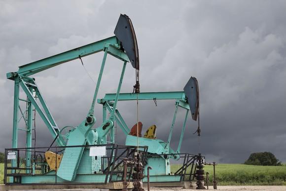Two green oil wells sitting under a dark stormy grey sky.