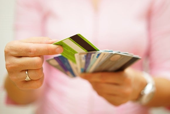 A woman holding a stack of credit cards.
