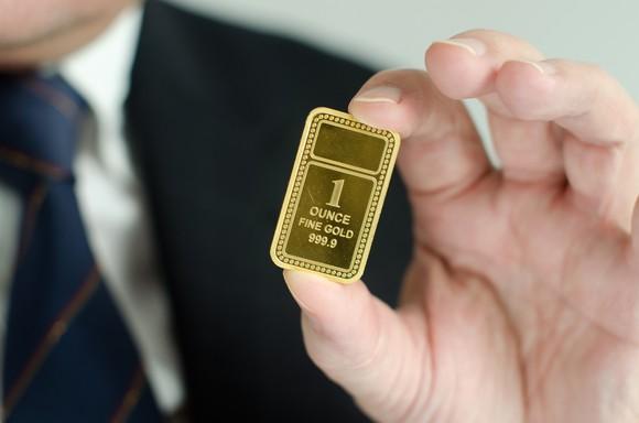 A man holding a 1 ounce gold ingot.