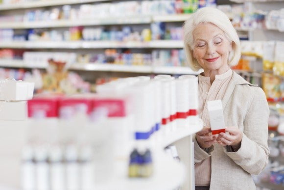A senior woman shopping in the health and beauty aisle of a pharmacy store.