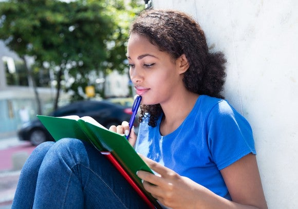 A young woman leans outdoors against a wall, knees drawn up, reading a book as she rests a pen against her chin.