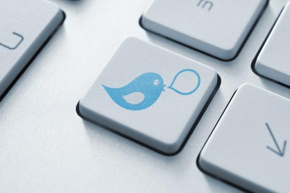 Computer with Twitter bird logo on keyboard key.