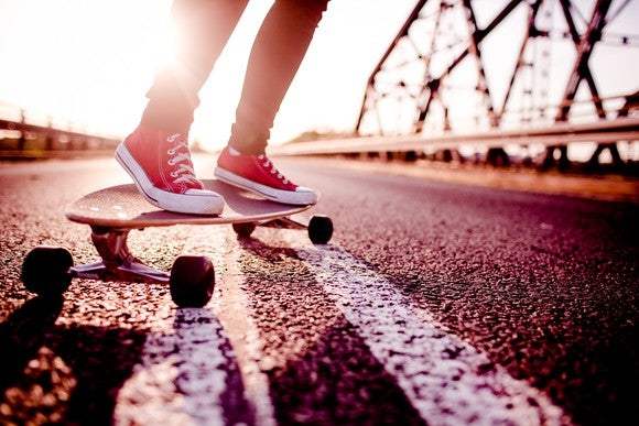 A person in athletic shoes riding a longboard
