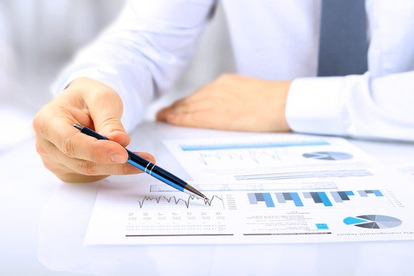Hand holding a pen on top of a piece of paper with several graphs and charts.