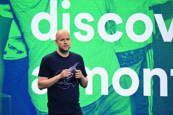 Spotify CEO Daniel Ek stands on stage at a press conference with a blue and green backdrop of people dancing