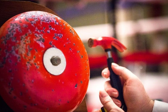 closeup of a red boxing bell and a hand hitting it with a small red hammer.