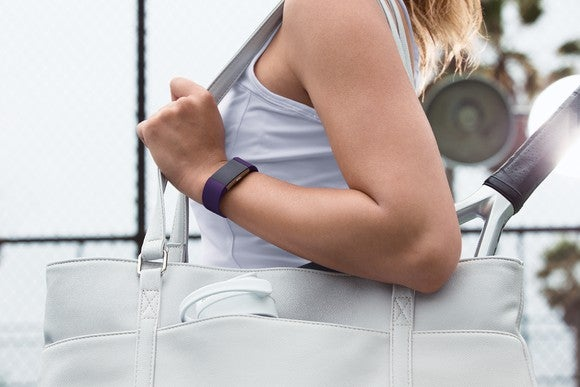 A woman wears a Fitbit Charge 2.
