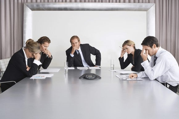 Management team of five people sitting around a conference table looking worried