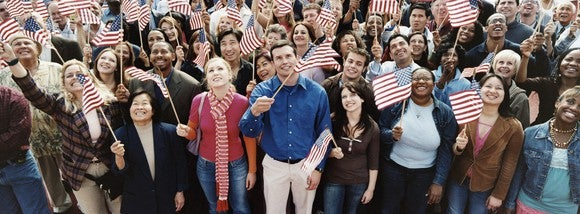 Dozens of people holding U.S. flags at a group gathering.