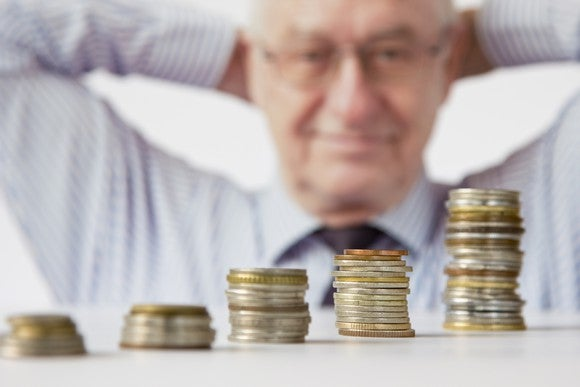 Man of retirement age looking at successively larger stack of coins.