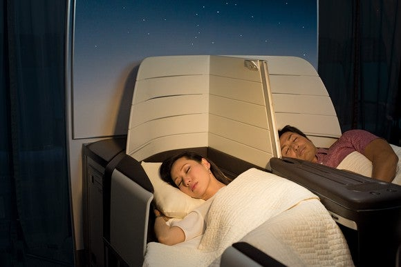 A man and a woman sleeping in lie-flat airplane seats