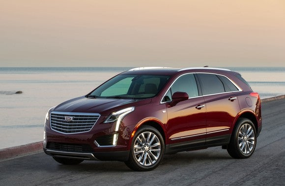 A dark red 2018 Cadillac XT5, a midsize crossover SUV, parked on a beach.