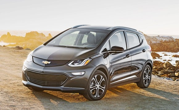 A black 2018 Chevrolet Bolt EV parked on a sunny beach.