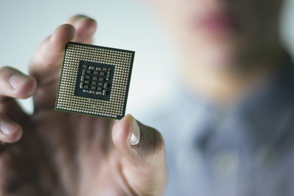 A hand holding what looks like an Intel microprocessor