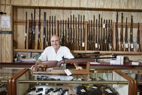 Man in front of a firearms display at a gun store