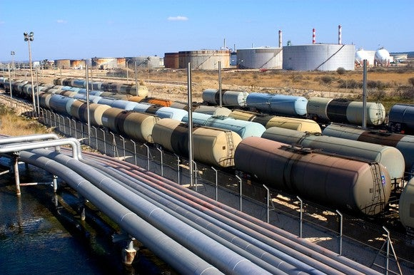 Crude oil logistics featuring tankers, railcars, and a pipeline.