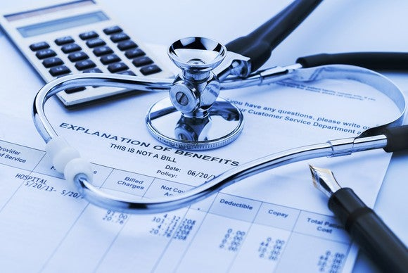 Health insurance benefits form with stethoscope, calculator, and pen on top.