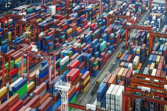 An overhead view of containers lined up at a port.