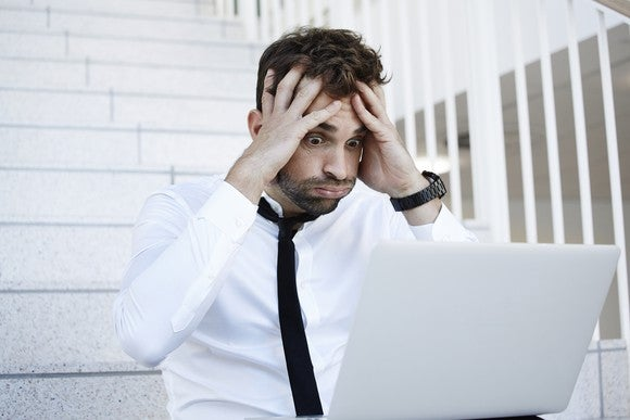 A man making an anxious expression while looking at an open laptop.