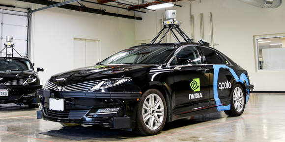 A self-driving car parked in a brightly lit room with the NVIDIA logo painted on the side door.