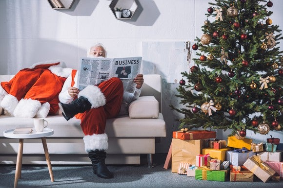 Santa reading the business section of the newspaper