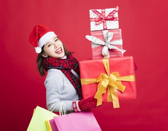 A woman holding a stack of presents