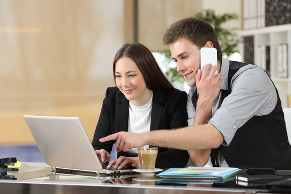 A pair of young business people working together using a computer and a smartphone.
