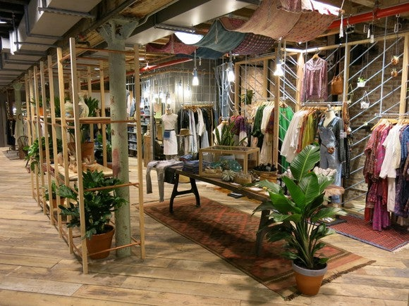 A scene inside an Urban Outfitters store where clothing and plants are displayed.