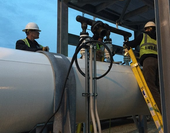 Enbridge workers testing a pipe.