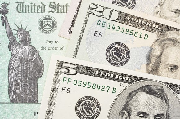 Tax refund check with bills of U.S. currency on top.